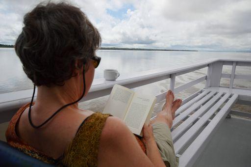 Uma viajante descansando no barco e curtindo a viagem pelas Belezas do rio Negro