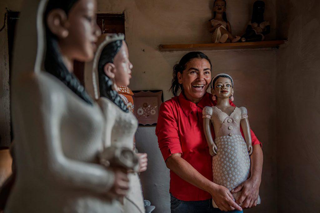 uma mulher segurando sua boneca de artesanato em barro no vale do jequitinhonha - esse roteiro faz parte do pacote do barro à arte