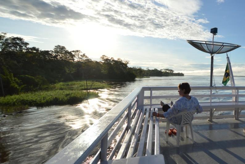 nossa viajante contemplando o final da tarde enquanto navega pelas belezas do rio Negro