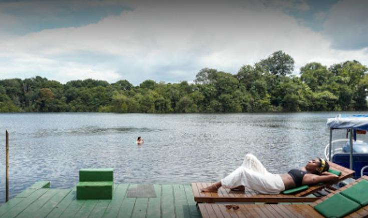 turista descansando no flutuante em frente ao manati lodge na área comum de lazer