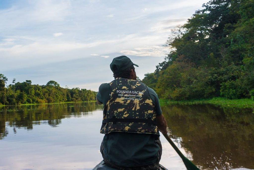 guia de selva remando sua canoa na floresta alagada na reserva de mamiraua