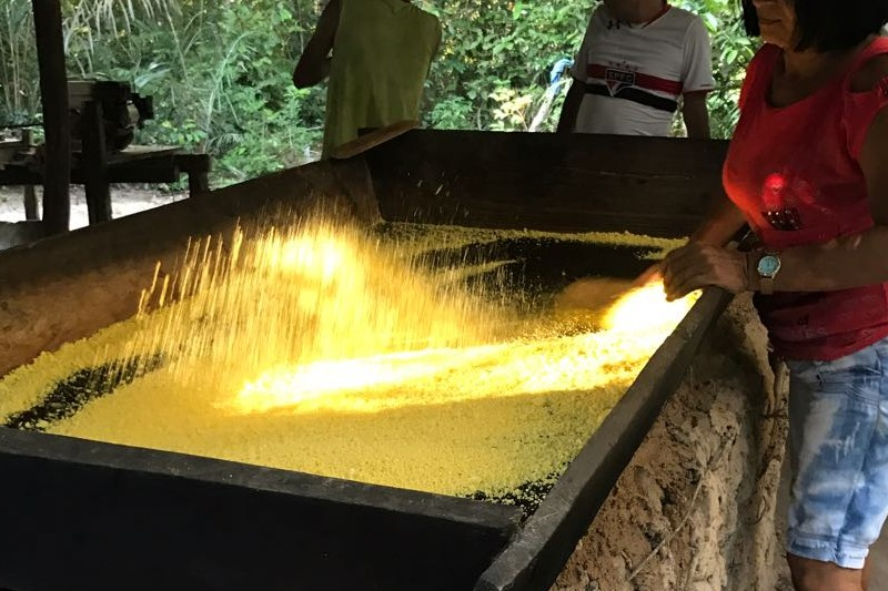 uma mulher fazendo farinha de mandioca no tacho